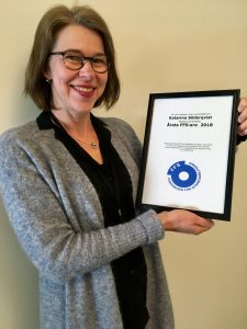 Foto av Katarina som håller upp den inramade utmärkelsen/diplomet